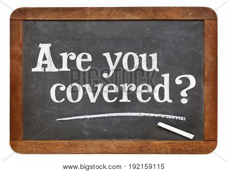 Are you covered question - white chalk text on a vintage slate blackboard, insurance concept