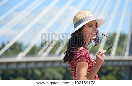 Girl rests on the river in the city. Background bridge