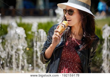 The girl is eating ice cream. Background fountain