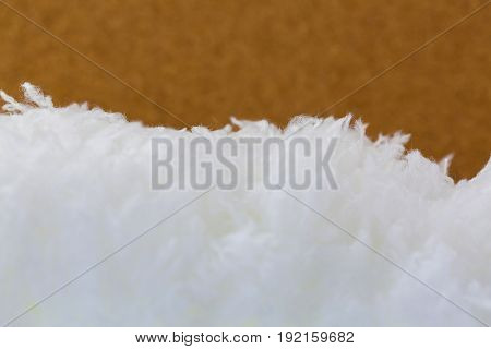 Closeup texture of soft fluffy white cloud like fur microfiber fabric on blurred brown cork background