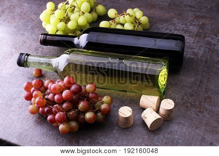 Bottle Of White And Red Wine, Grape And Corks On Wooden Table