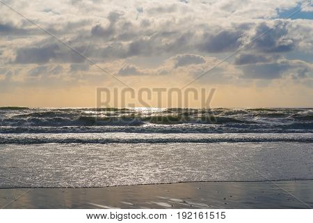 Image of sunlit waves at the beach.