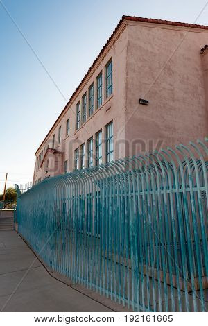 Pink Building with Windows and Teal Security Fence