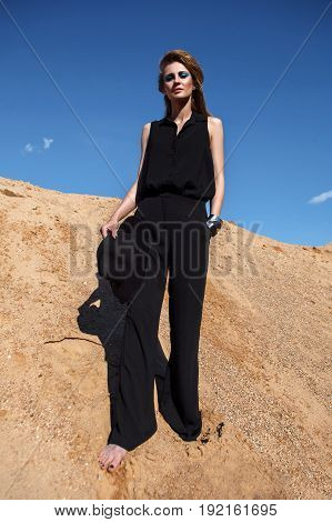 fashion beautiful girl in black clothes standing on a sand hill
