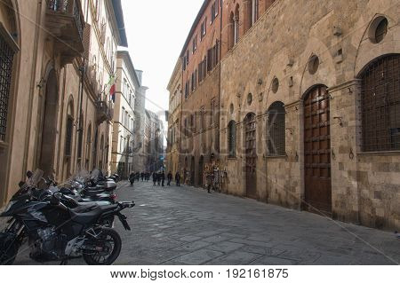 Italy Siena - December 26 2016: the street view of Siena with typical medieval buildings people motorbikes on December 26 2016 in Siena Tuscany Italy.
