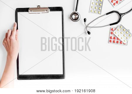 doctor's work desk in hospital with notepad and stethoscope on white background top view mockup