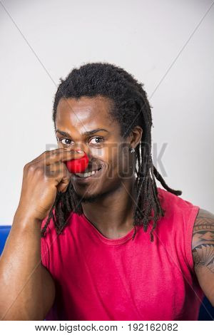 Handsome young man smiling and touching red clown nose, sitting on couch