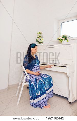 pregnancy, motherhood, people and expectation concept - close up of happy pregnant woman with big belly indoors.