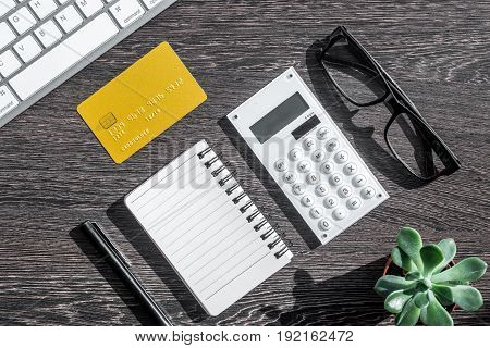 savings, finances and economy set for accountant or banker with notebook on dark wooden table background top view mock up