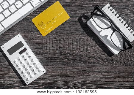 online purchasing with credit cards and notebook on dark wooden manager desk background top view mock-up