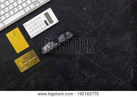 accountant or banker desk with calculator, keyboard and glasses on dark background top view mockup