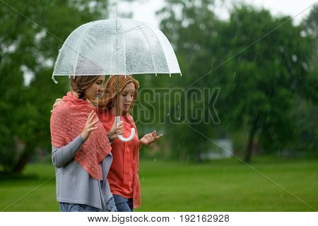 Two women walking park in rain and talk. Friendship and people communication. Rainy day in summer