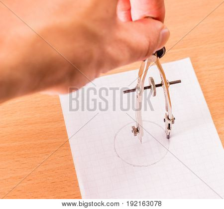 Hand holds the compasses and draws a circle on a piece of paper on a wooden background