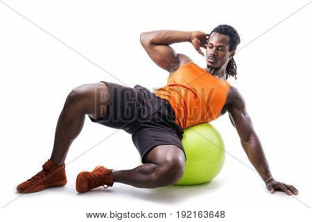 Muscular man holding inflatable fitness ball, looking at camera, leaning on it isolated on white background