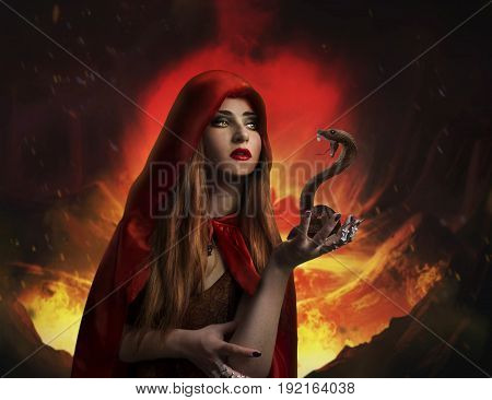 Pretty woman in red cloak holding a snake on volcano background photo.
