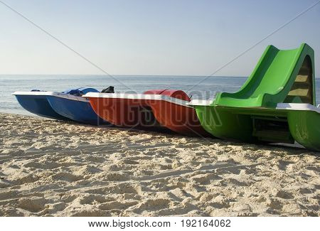 Three catamarans on the beach. Red, green and blue catamarans on the beach photo.