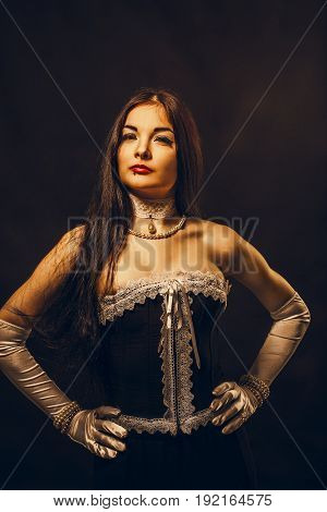 Pretty young countess in corset posing over dark backgkround