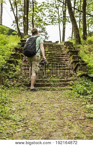 Tourist man holds a retro camera in his hands walking in a summer forest park along an old grass-covered cobblestone path and a moss-grown steps.