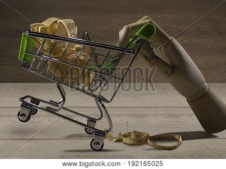 Wooden hand with shopping cart. Hand of a wooden puppet holding a shopping cart of sawdust photo.