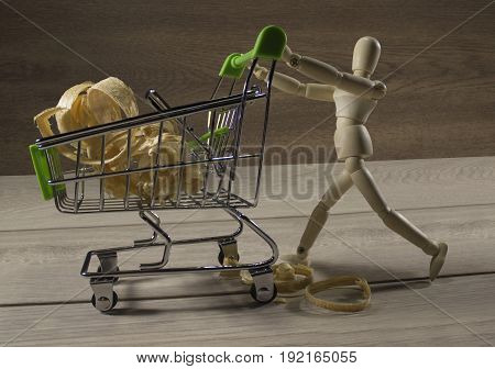 Wooden puppet going shopping with shopping cart of sawdust photo.