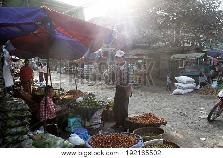 Zegyo MARKET/MANDALAY, MYANMAR JAN 22: A vegetable vedor is chatting with a customer while her collegue is havin a nap in the late afternoon January 22, 2016, Zegyo Market, Mandalay.