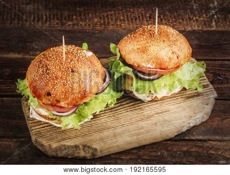 Delicious homemade burgers with beef patty, lettuce, tomato, cheese, red onion served with white sauce and ketchup, on wooden cutting board. Top view