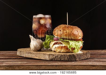 Homemade burger with beef patty, lettuce, tomato, cheese and red onion served with garlic, white sauce and ketchup, on wooden cutting board and mug of cola with ice. copyspace