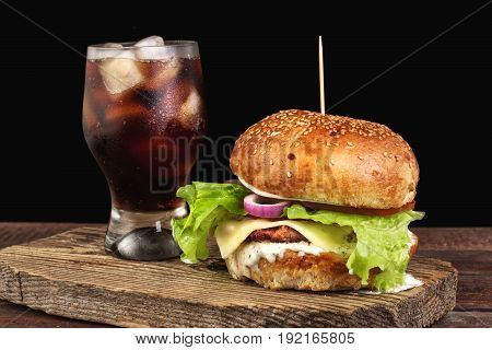 Homemade burger with beef patty, lettuce, tomato, cheese and red onion served with mug of cola with ice, white sauce and ketchup, on wooden cutting board.