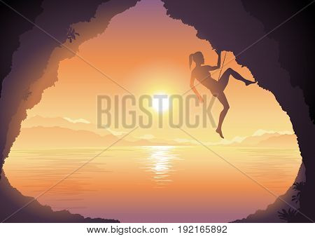 Silhouette of woman climbing on a cliff on nature background with beautiful sunset