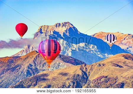 Morning flight of the three hot air balloons above the mountains.
