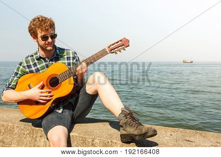 Young man hipster playing guitar by sea ocean water. Handsome guy in sunglasses relaxing on summer vacation.