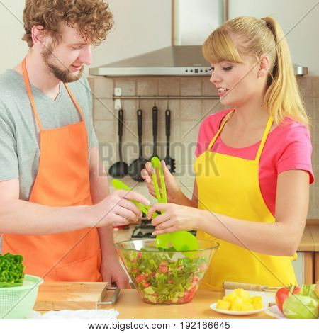 Healthy eating vegetarian food cooking dieting and people concept. Couple in kitchen at home preparing meal mixing fresh vegetables salad