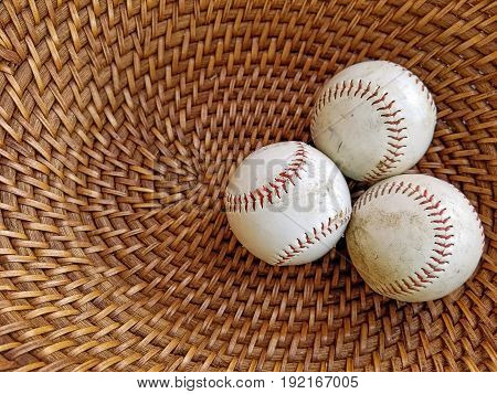 three worn baseballs in brown wicker basket