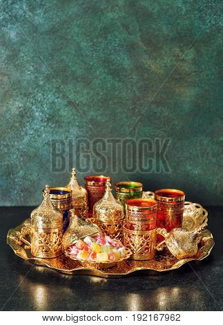 Arabic tea coffee table golden dishes. Oriental hospitality. Ramadan kareem. Vintage style toned picture