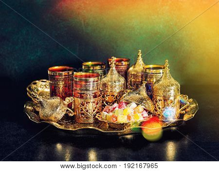 Tea table with golden dishes. Oriental hospitality. Ramadan kareem. Vintage style toned picture with light leaks