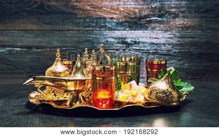 Tea glasses with mint leaves. Golden decorations and oriental lantern. Ramadan kareem. Vintage style toned picture