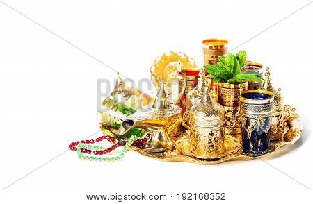 Tea service and green mint leaves. Ramadan decoration with lantern. Vibrant colors