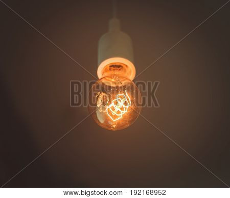 Old electric lightbulb in darkness. incandescent lamp