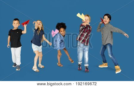 Diverse Group Of Kids Launching Paper Plane