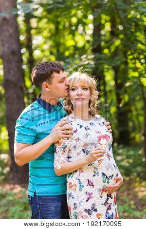 Happy and young pregnant couple hugging in nature