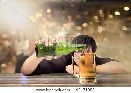 Young male hand holding beer bottle and fill the glass Asian man pouring beer on bar in pub party