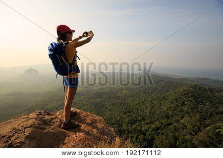 woman hiker taking photo with smartphone on mountain peak