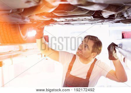 Male repair worker examining car in workshop