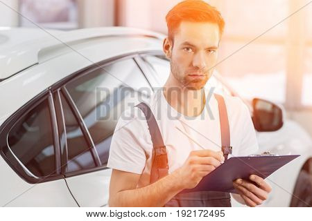 Portrait of confident male maintenance engineer writing on clipboard in workshop