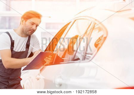 Automobile mechanic writing on clipboard while examining car in repair shop