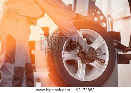 Midsection of male mechanic repairing car's wheel in repair shop