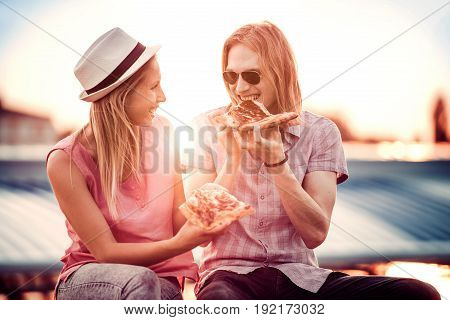 Couple sharing pizza and eating together outdoors.