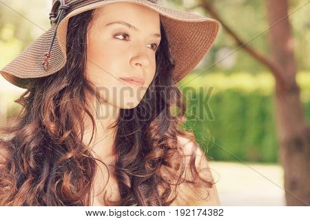 Beautiful young woman in sunhat looking away in park