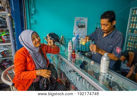 BALI, INDONESIA - MARCH 08, 2017: Unidentified man using syringes and pipettes mixing essences to prepare perfumes, while a woman is buying a perfume in the perfume store in Denpasar Indonesia.