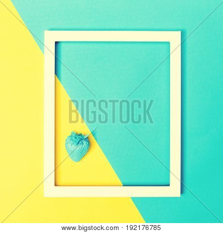 Painted blue stawberry on a bright split color background